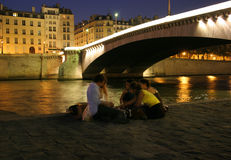 Night Along the Seine. A group of friends unwinding along the Seine River in Paris, France Royalty Free Stock Photos