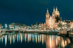 Night Amsterdam canal and Basilica Saint Nicholas royalty free stock photo