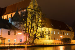 Night architecture in city. Church on the bank of river. Stock Photos