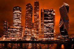 Night architecture - skyscrapers with glass facade. Modern buildings in red tone stock photography