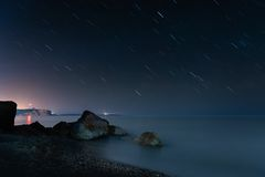 Night beach under star trails Royalty Free Stock Images