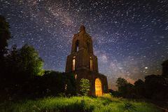 Night bell tower ruin in forest at starry night with internal light. Night brick bell tower ruin in forest at starry night with mystical internal light stock photos
