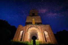 Night bell tower ruin in forest at starry night and man with flashlight under it.  royalty free stock photography