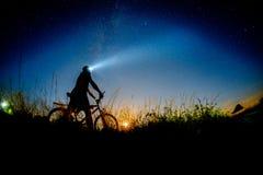 Night biker. Man biking and observing the nightsky Stock Photo
