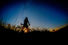 Night biker. Man biking and observing the nightsky Royalty Free Stock Images