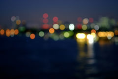 Night blurred lights in city with little light bokeh reflection. Abstract background. Night blurred lights in city with little light bokeh reflection on river Stock Photos