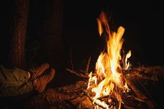 Night bonfire in tourist camp and legs of traveler. Tourism conc Royalty Free Stock Photos