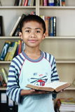 Night Book Reading. A boy holding a book at home library in pajamas implying reading book at night Stock Photo