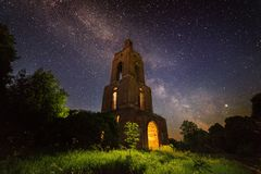 Night bell tower ruin in forest at starry night with internal light. Night brick bell tower ruin in forest at starry night with mystical internal light stock image