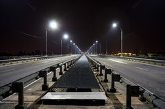Night bridge with lanterns, the road goes into the distance at night royalty free stock images