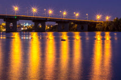 Night bridge lights reflected in river water. HDR Stock Photos