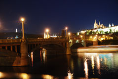 Night bridge over the river in Prague. Prague night lights reflected in the river Stock Photos