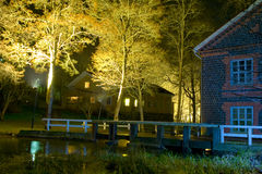 Night building and footbridge. A night view of lighted buildings and a footbridge over water in the village of Fiskars, Finland Royalty Free Stock Images