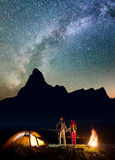 Night camp. Romantic pair hikers holding hands, standing near camping and enjoying incredibly beautiful starry sky Royalty Free Stock Photos