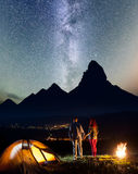 Night camping. Charming hikers family - man and woman holding hands, standing near camp and enjoying starry sky Royalty Free Stock Images