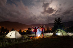 Night camping. Couple stands holding hands lifting up Stock Photo