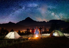 Night camping. Couple tourists standing and holding hands lifting up Royalty Free Stock Photo