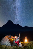 Night camping. Family - man and woman sitting near tent and campfire and enjoying incredibly beautiful starry sky royalty free stock photography