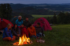 Camping people watching campfire together beside tents Stock Photography