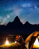 Night camping. Happy couple hikers sitting and kissing near a campfire and tent under the stars and Milky way Royalty Free Stock Image