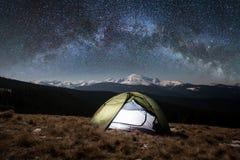 Night camping. Illuminated tourist tent under beautiful night sky full of stars and milky way Royalty Free Stock Photo
