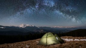 Night camping. Illuminated tourist tent under beautiful night sky full of stars and milky way Stock Photos