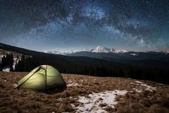 Night camping. Illuminated tourist tent under beautiful night sky full of stars and milky way Royalty Free Stock Image