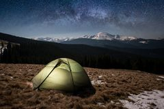 Night camping. Illuminated tourist tent under beautiful night sky full of stars and milky way Stock Photo