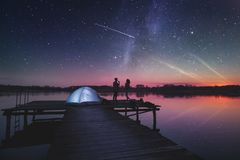 Night camping on the lake. Combination of high ISO, noisy image of a starry sky and image of a couple camping on lake docks at dusk, standing next to a tent stock image