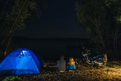 Night camping on lake shore. Man and woman is sitting. Couple tourists enjoying amazing view of night sky full of stars. Blue tent stock photography