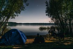 Night camping on lake shore. Man and woman is sitting. Couple tourists enjoying amazing view of night sky full of stars. Blue tent royalty free stock photo