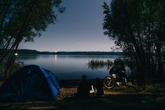 Night camping on lake shore. Man and woman is sitting. Couple tourists enjoying amazing view of night sky full of stars. Blue tent royalty free stock photography