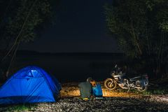 Night camping on lake shore. Man and woman is sitting near campfire. Couple tourists enjoying amazing view of night sky full of stock photos