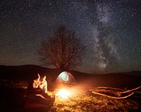 Night camping in mountains. Couple hikers having rest near campfire, tourist tent under starry sky. Camping night in mountains. Couple hikers boy and girl Stock Image