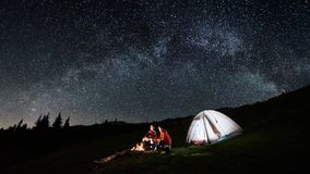 Couple tourists near campfire and tents under night sky full of stars and milky way. Night camping in the mountains. Couple tourists have a rest at a campfire royalty free stock photos