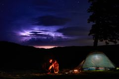 Night camping in the mountains. Couple tourists have a rest at a campfire near illuminated tent stock photography