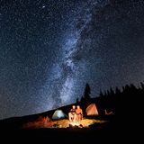 Couple tourists near campfire and tents under night sky full of stars and milky way Royalty Free Stock Photo
