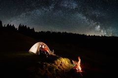 Couple tourists near campfire and tents under night sky full of stars and milky way Royalty Free Stock Photography
