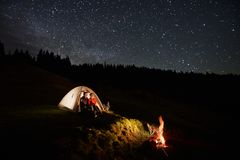 Tourists near campfire and tent under night starry sky stock photo