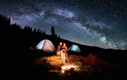 Couple tourists near campfire and tents under night sky full of stars and milky way Stock Images
