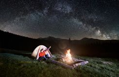 Couple tourists near campfire and tents under night sky full of stars and milky way Stock Photos