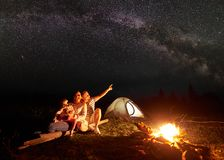 Tourist family with daughter having a rest in mountains at night under starry sky with Milky way. Night camping in mountains. Family sitting in front of shining Royalty Free Stock Photography