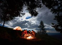 Evening camping in the mountains. Friends are sitting around fire with beer enjoying holiday. Night camping in the mountains. Group of friends hikers having a royalty free stock images