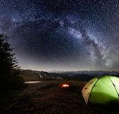Night camping in the mountains. Illuminated tent and campfire under night sky full of stars and milky way Royalty Free Stock Photo