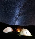 Couple tourists near campfire and tents under night sky full of stars and milky way. Night camping in the mountains. Rear view of romantic couple tourists have a royalty free stock image