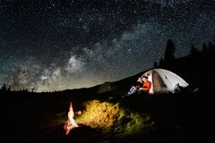 Couple tourists near campfire and tents under night sky full of stars and milky way. Night camping in the mountains. Romantic couple tourists enjoying in the stock photo