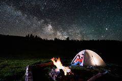 Couple tourists near campfire and tents under night sky full of stars and milky way Royalty Free Stock Image