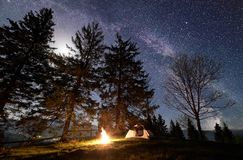 Night camping in mountains. Tourist tent by campfire near trees under blue starry sky, Milky way. Night camping in mountains. Tourist tent by brightly burning royalty free stock photo