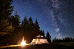 Night camping in mountains. Tourist tent by campfire near forest under blue starry sky, Milky way. Night camping in mountains. Tourist tent by brightly burning royalty free stock photos