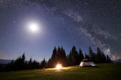 Night camping in mountains. Tourist tent by campfire near forest under blue starry sky, Milky way stock image